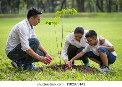 happy asian Family, parents and their children plant sapling tree together in park . father mother and son,boy having fun and laughing outdoors . cheerful . volunteering, charity, people,ecology
