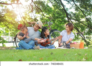 Happy asian family picnic in the garden togetherness relaxation concept