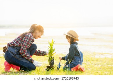 Happy Asian family planting tree at natural park  , woman with little cute girl planting tree at park ,  Enviroment  ecology   green world healthy family lifestyle Concept