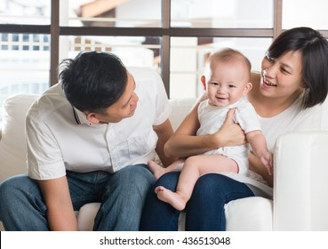 Happy Asian Family Playing with baby in the living room