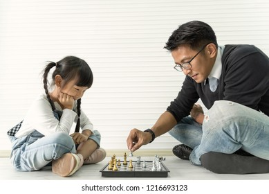 Happy asian family playing chess together.