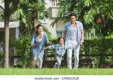 Happy Asian family playing with daughter girl in green garden