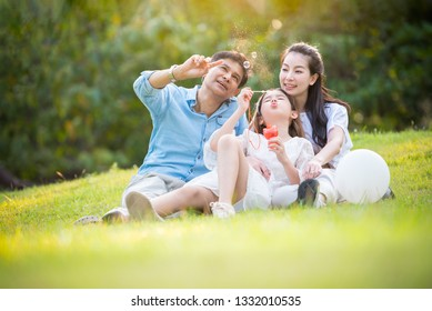 Happy asian family playing enjoy funny time together in public park with sunlight sky background.
