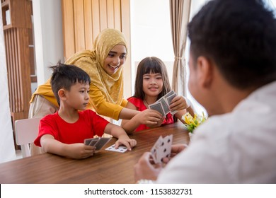 happy asian family playing fun card game together at home