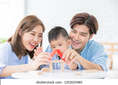 happy asian family playing with toy blocks and