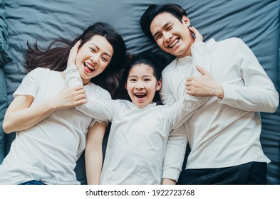 Happy Asian family portrait with mother, father and daughter