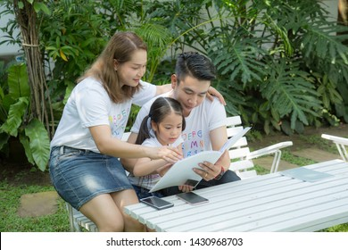 Happy Asian family reading a book with daughter in the garden at home.Family relaxing in the garden, happy asian family concept