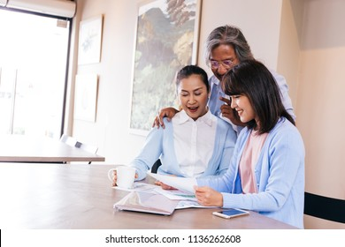 Happy Asian family reading and receiving a good news letter together at home, Information may contain tax refund money, university admission, lottery winning, test results or invitation letter