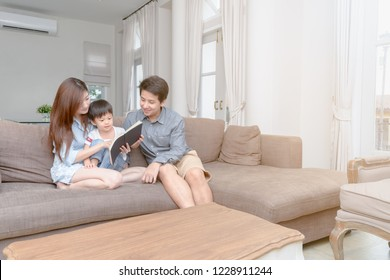 Happy asian family reading storybook at home in the living room, learning and education concept