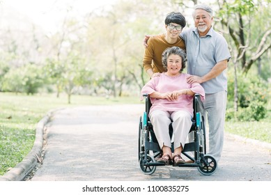 Happy Asian family, senior and young man, walking together in the park using wheelchair