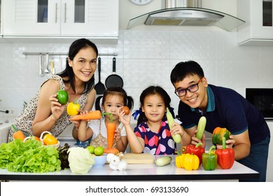 Happy Asian family show vegetable in hand, eating healthy concept