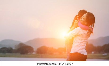 Happy Asian family .Silhouette Happy mother and daughter with embracing