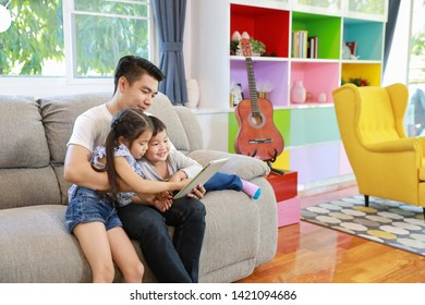 Happy Asian family single dad is teaching his childrens son and daughter how to use tablet while sitting on grey sofa in living room with happy smiling faces