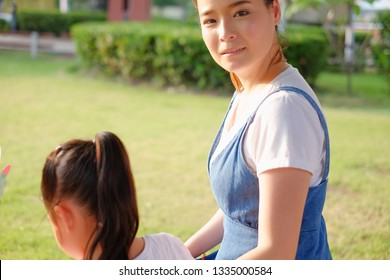 Happy asian family single mom and small daughter in the Park