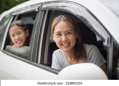 Happy Asian family sitting in the car