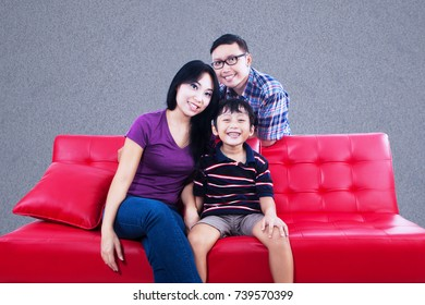 Happy asian family sitting on couch in front of grey background