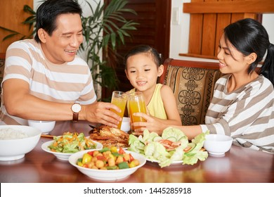 Happy Asian family sitting at the table together with their daughter having dinner and toasting with glasses of orange juice at home