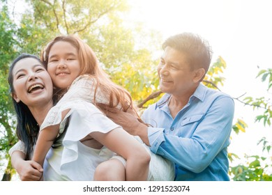 Happy Asian family spending time together in the park