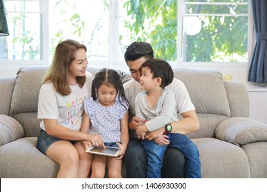 Happy Asian family teaching their childrens son and daughter how to use tablet while sitting on grey sofa in living room with smiling faces