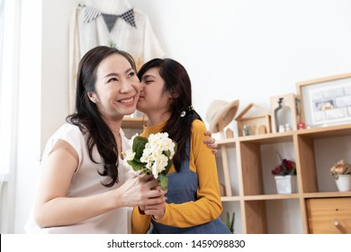 Happy Asian family Teenage daughter are kiss the cheek and give flower bouquet to her mom in a room with nature sunlight at home. Show Love, Happy Mother's Day concept