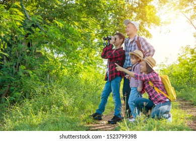 Happy asian family trekking in forest together on vacation.