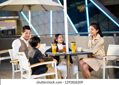 happy asian family with two children relaxing talking having drinks and desserts at an outdoor coffee place.
