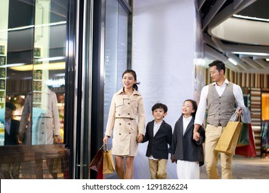 happy asian family with two children walking in shopping mall