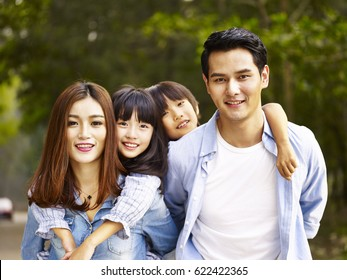 happy asian family with two children taking a walk in wooded park.