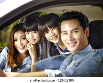 happy asian family with two children riding in a car