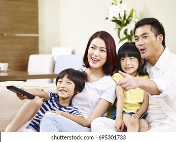 happy asian family with two children sitting on sofa watching TV together.