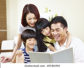 happy asian family with two children sitting on sofa reading a book together.