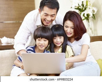 happy asian family with two children sitting on couch at home using laptop computer together.