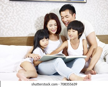 happy asian family with two children sitting in bed reading a book together.