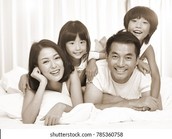 happy asian family with two children having fun in bed at home, black and white sepia toned.