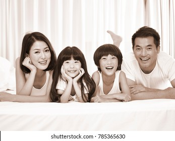 happy asian family with two children lying on front in bed looking at camera smiling, black and white sepia.