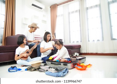 Happy asian family using laptop computer at home planning vacation travel trip togetherness relaxation concept