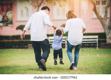 Happy Asian Family Walking and Hold Hands with Son in the Park - Lifestyle Concept