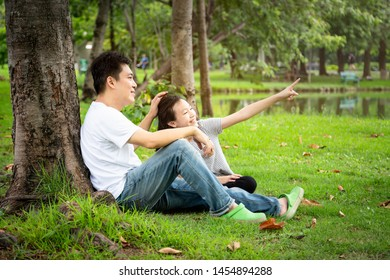 Happy asian family,adult man,cute child girl with love,smiling,hand of father caress his hair,head little daughter in outdoor park,sitting under the tree in nature,father's day,family,love concept