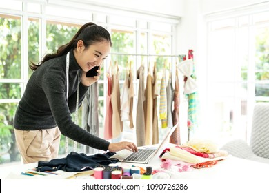 Happy asian fashion designer holding smartphone look excited with good news,notification,sale order or deal in laptop at modern office .Young creative tailor dress maker,stylish or seamstress concept.
