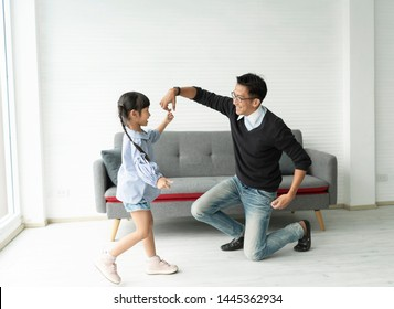 Happy asian father and daughter playing dance together in living room at home.