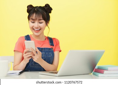 Happy Asian female student using her mobile phone at the table