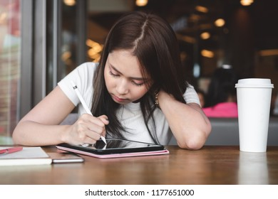 Happy asian freelancer woman working with digital tablet, touch pen, smartphone and cup of coffee on table at cafe. Smart girl using laptop for design online advertising. Digital marketing, Freelance.