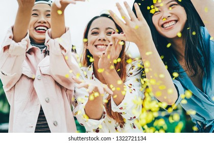 Happy Asian friends having fun throwing confetti outdoor - Young trendy people celebrating at festival event outside - Party, entertainment and youth holidays lifestyle concept