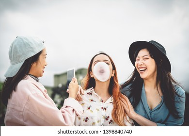 Happy Asian friends having fun chewing bubble gum outdoor - Young people playing and taking funny videos for social media - Friendship, Millennial generation, technology and youth lifestyle concept
