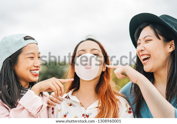 Happy Asian friends having fun chewing bubble gum outdoor - Young people playing and laughing together - Friendship, Millennial generation and youth lifestyle concept