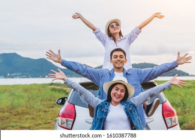 Happy Asian friends spread arms widely and breathed fresh air with happiness mood in on raod trip in car trunk. People lifestyle in long vacation trip concept. Outdoors nature and transportation