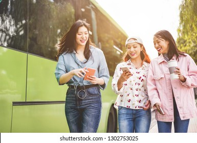 Happy asian friends using smartphones at bus station - Young students people having fun with technology trends after school outdoor - Friendship, university and trasports app concept - Focus on faces