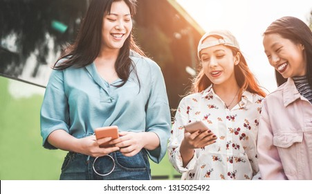 Happy asian friends using smartphones at bus station - Young women students people having fun with technology trends - Friendship and trasports app concept - Focus on left girls faces
