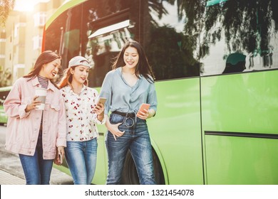 Happy asian friends using smartphones at bus station - Young students people having fun after school outdoor - Friendship, tech trends, university and trasports app concept - Focus on right faces
