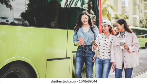 Happy asian friends using smartphones at bus station - Young students people having fun after school outdoor - Friendship, tech trends, university and trasports app concept - Focus on center gilr face